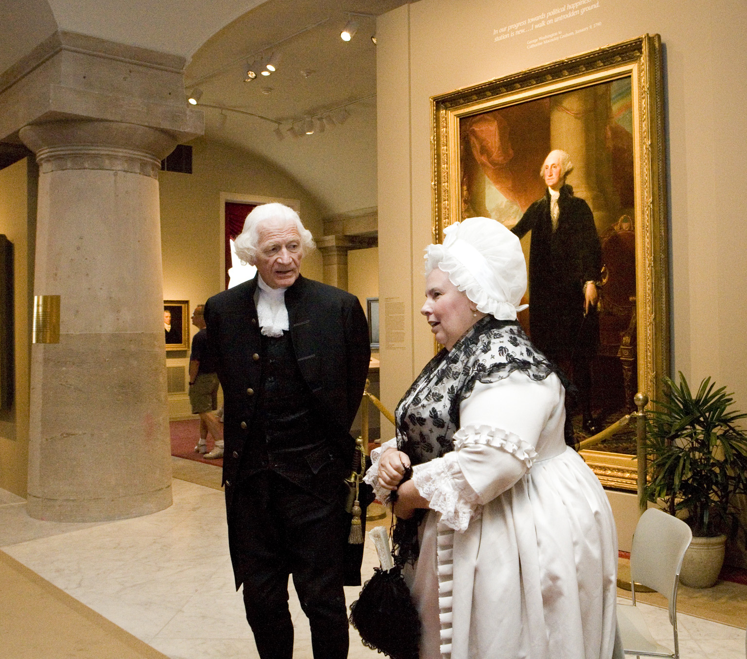 Two people dressed as George and Martha Washington appear in front of a George Washington portrait.