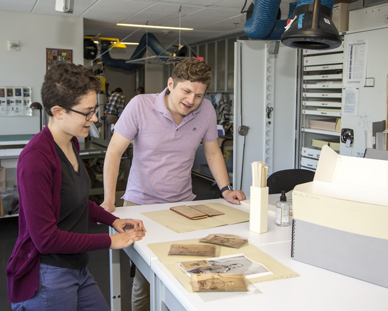 Archivist and Conservator are pictured in discussion in the Conservation Lab