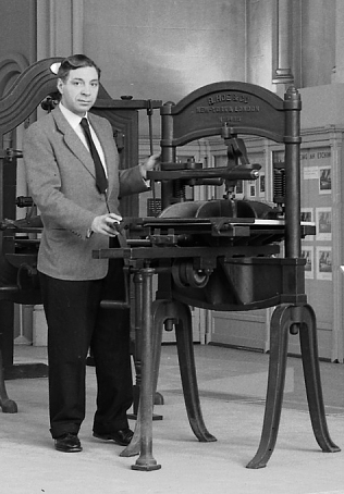 Black and white photograph of man in suit next to unknown metal object.