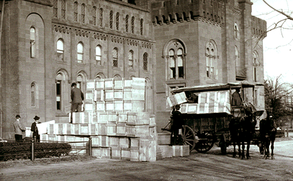 Men loading boxes of box on to a horse-drawn wagon