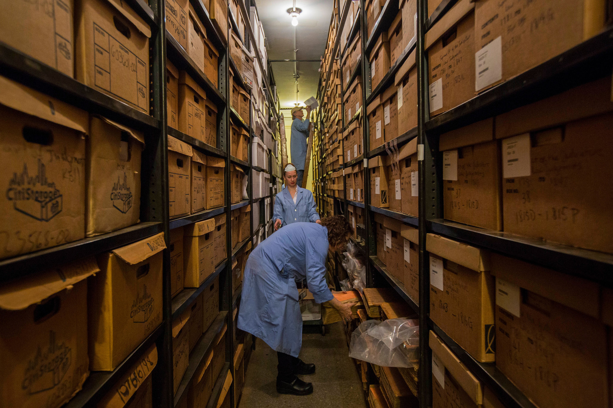 Color photo of archivists in lab coats moving old boxes.