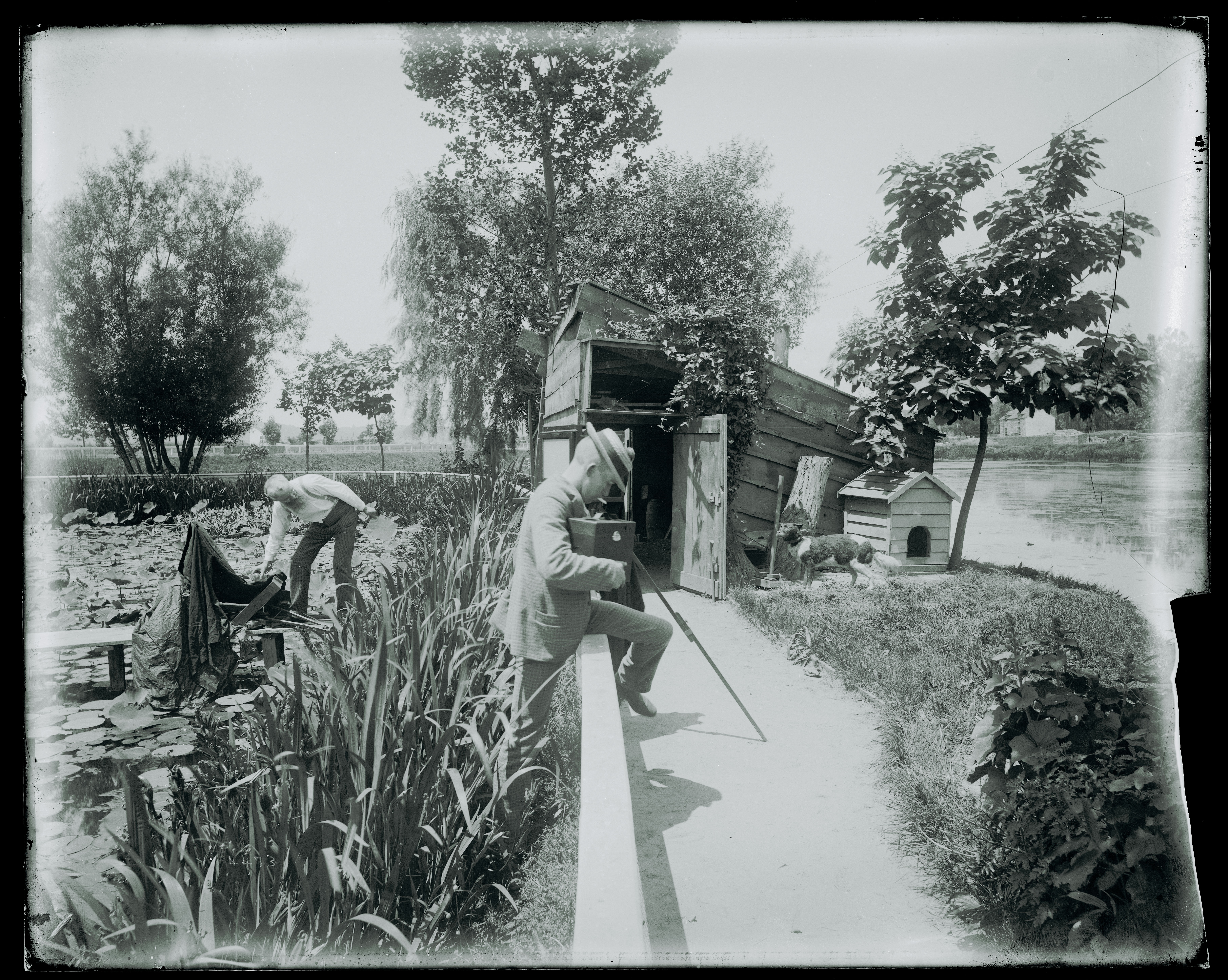 Photographers with photographic equipment by the U.S. Fish Commission fish hatchery ponds located ne