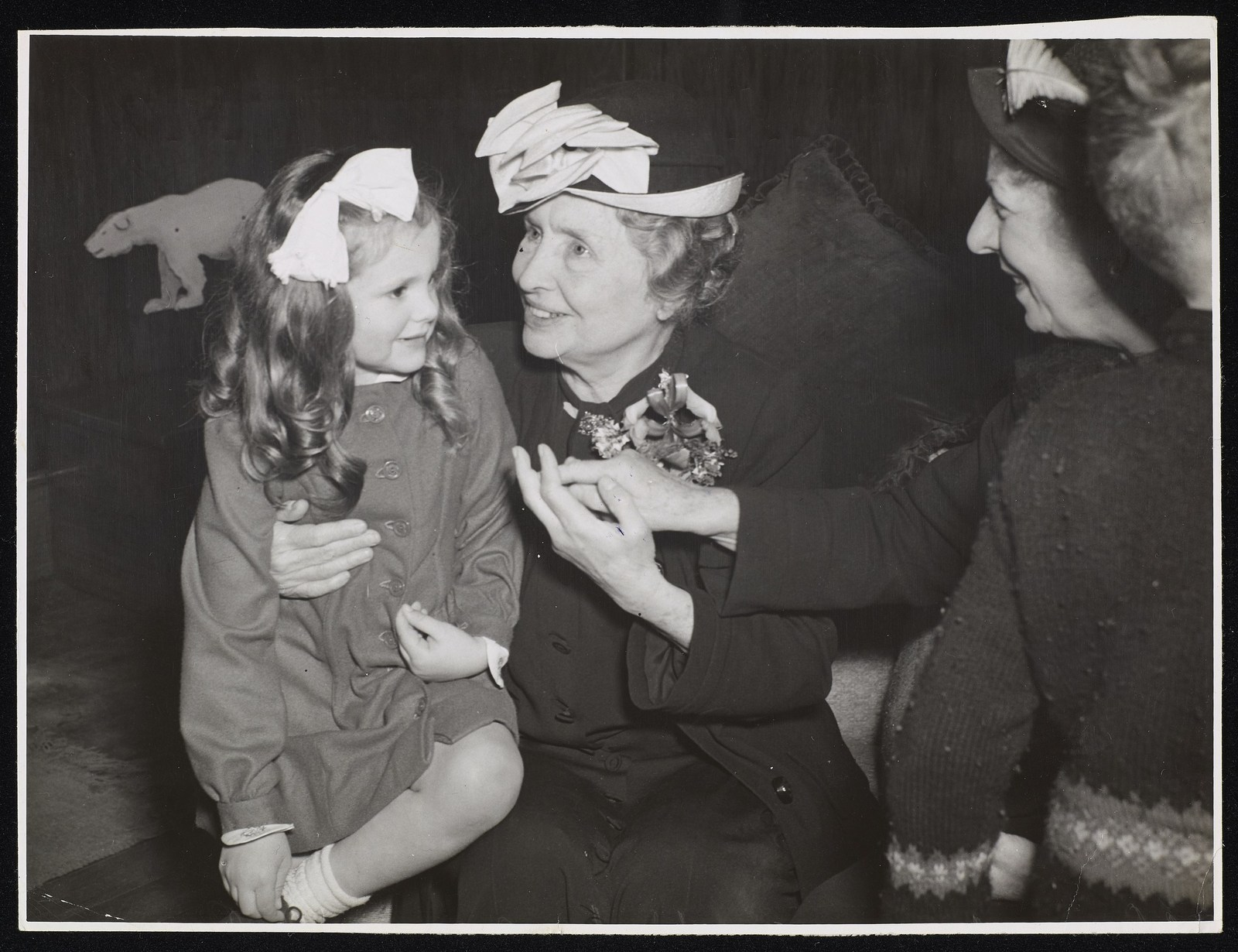 Girl smiling with bow in hair sitting next to Helen Keller who has her arm around her and is smiling