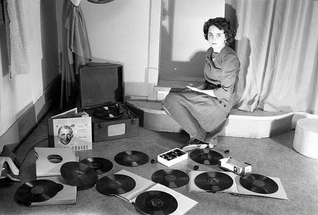 A young women posing with vinyl records and a record player. 1940s-1950s, Galt Museum & Archives, ht