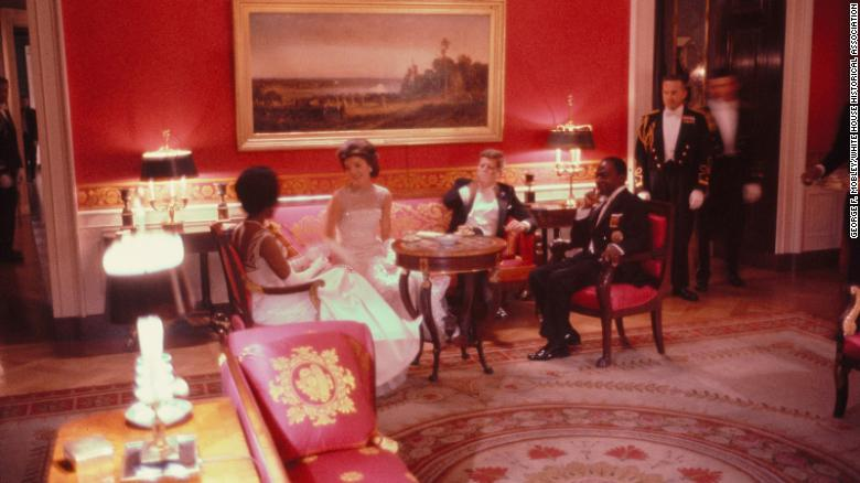 Black and white couple in formal dress seated on couch and chairs in room with red walls. JFK smokin
