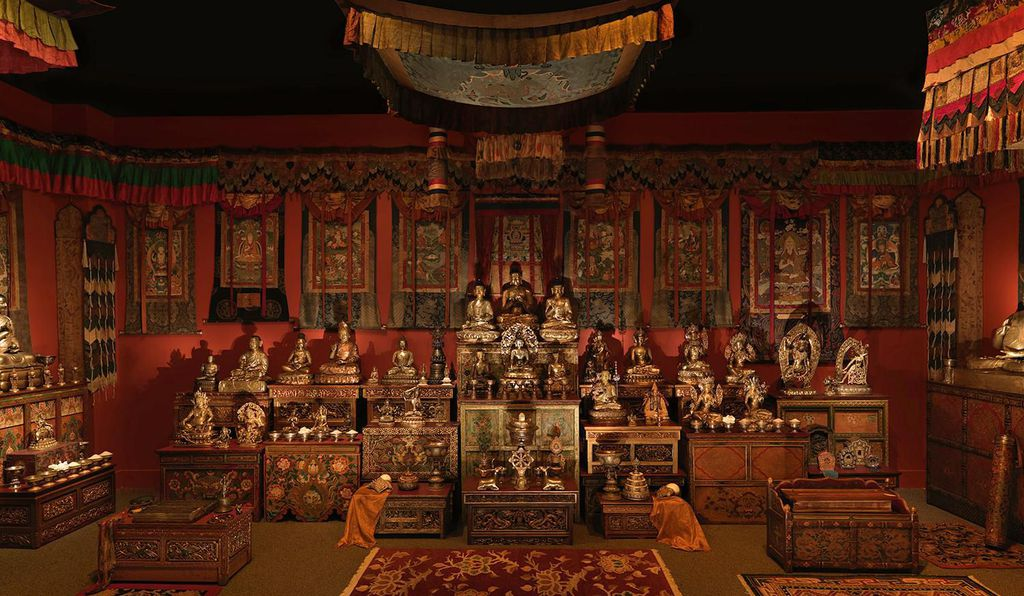 brightly enshrined orange/red room filled with brightly colored boxes with buddha statues on top