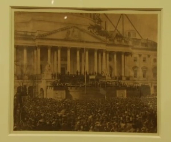 Sepia toned photograph of large crowd around U.S. Capitol as Abraham Lincoln is sworn in.