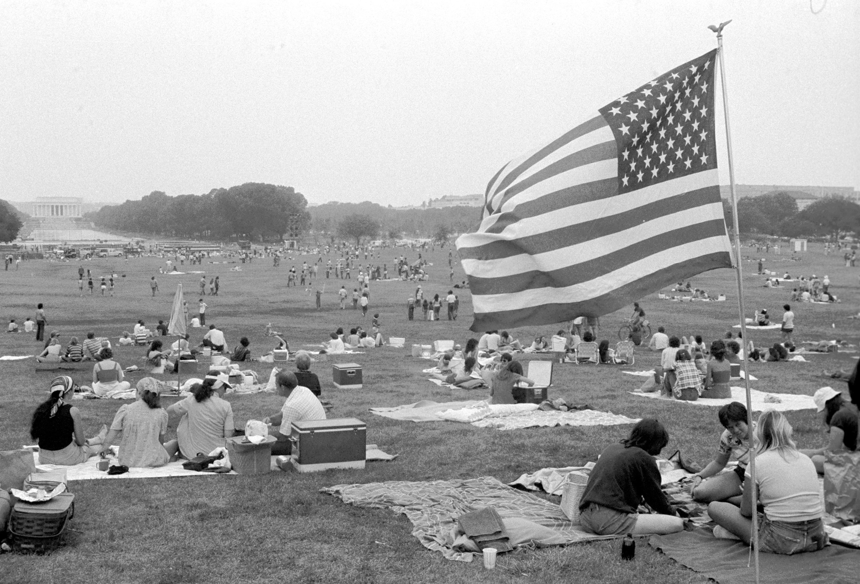 A group of people sit on a lawn with an American flag waving in the forefront.