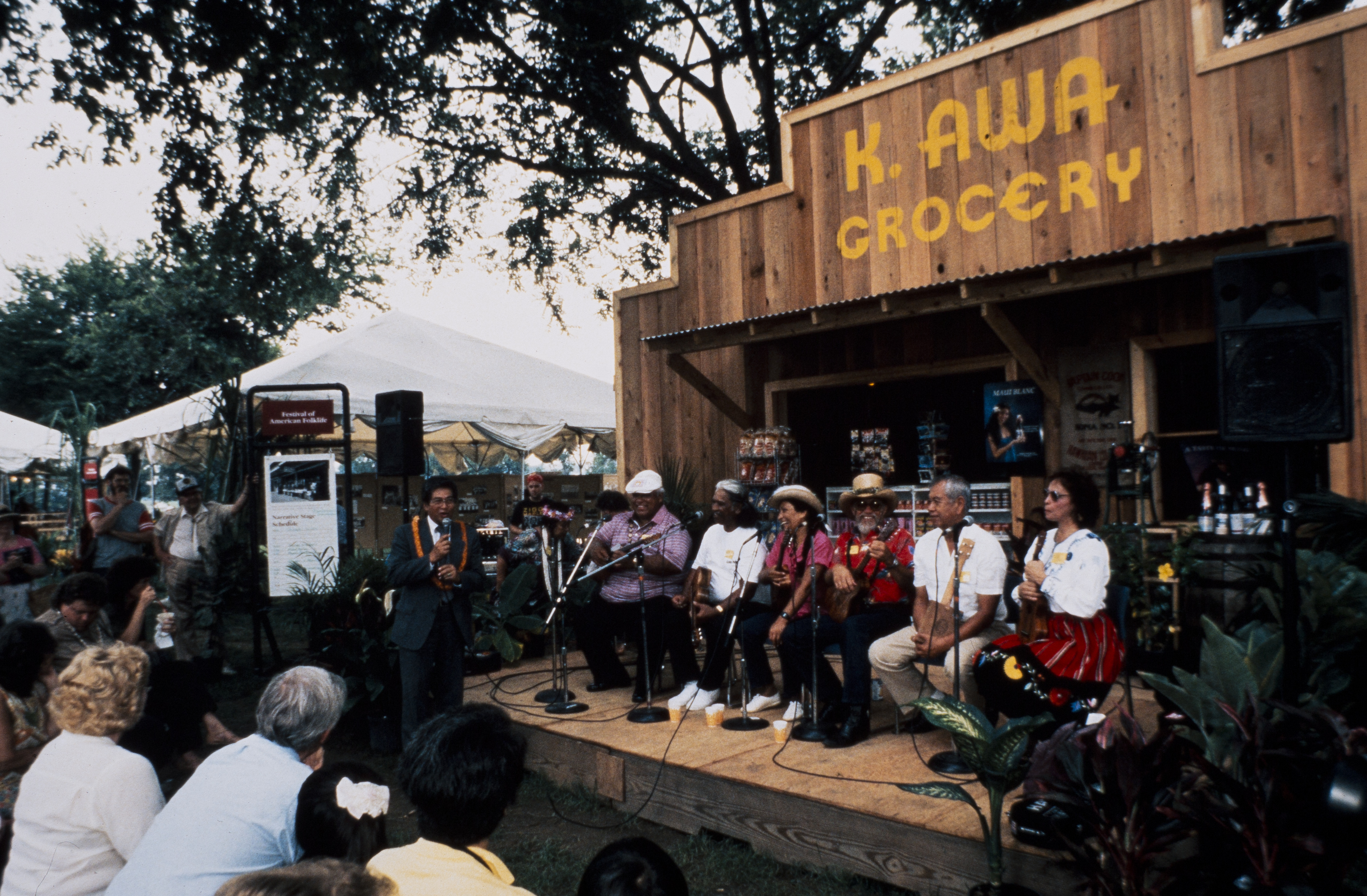 Six festival participants on wooden stage holding ukuleles with visitors looking on.