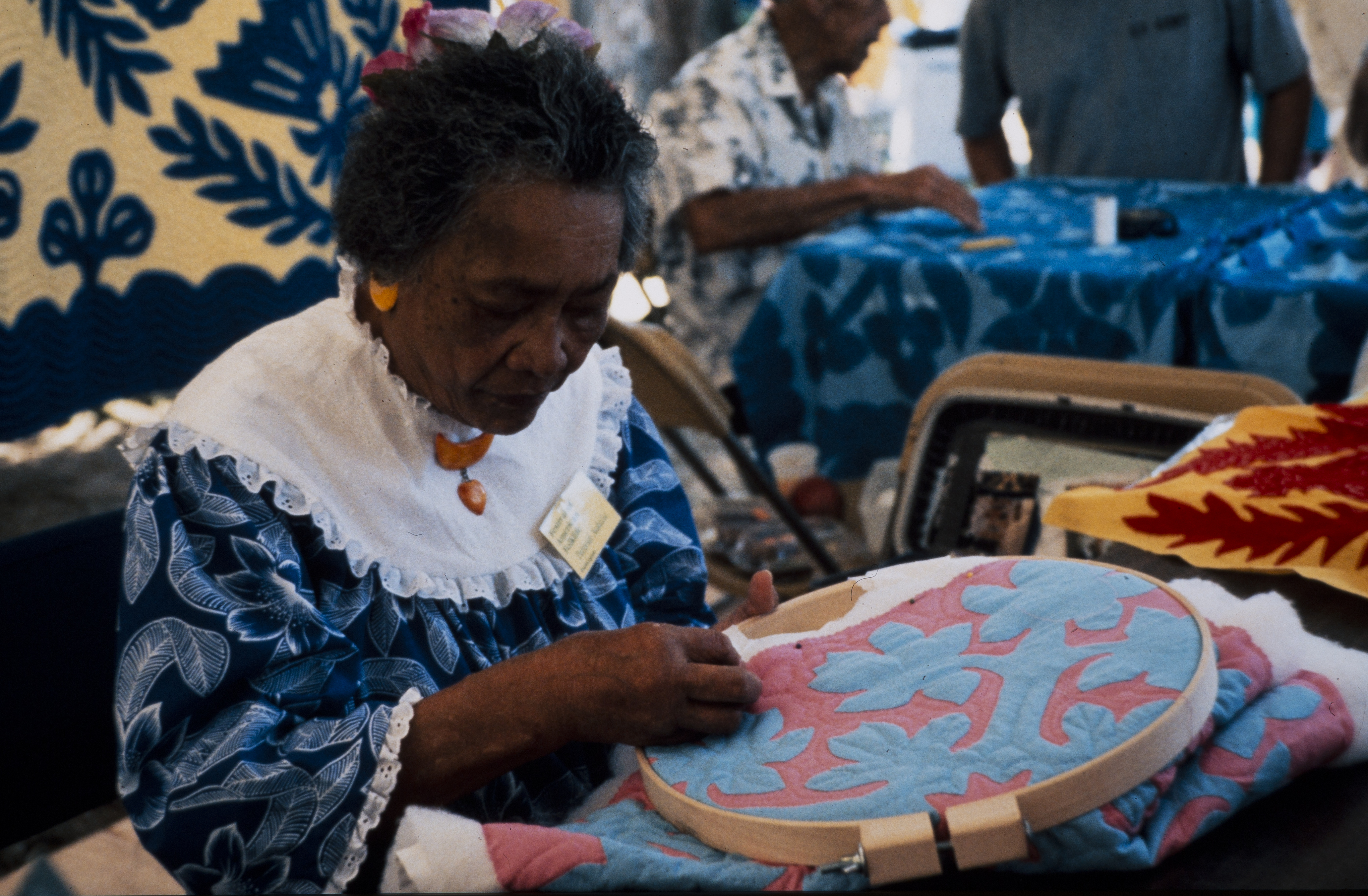 Festival participant seated quilting a quilt in a circular wooden frame.