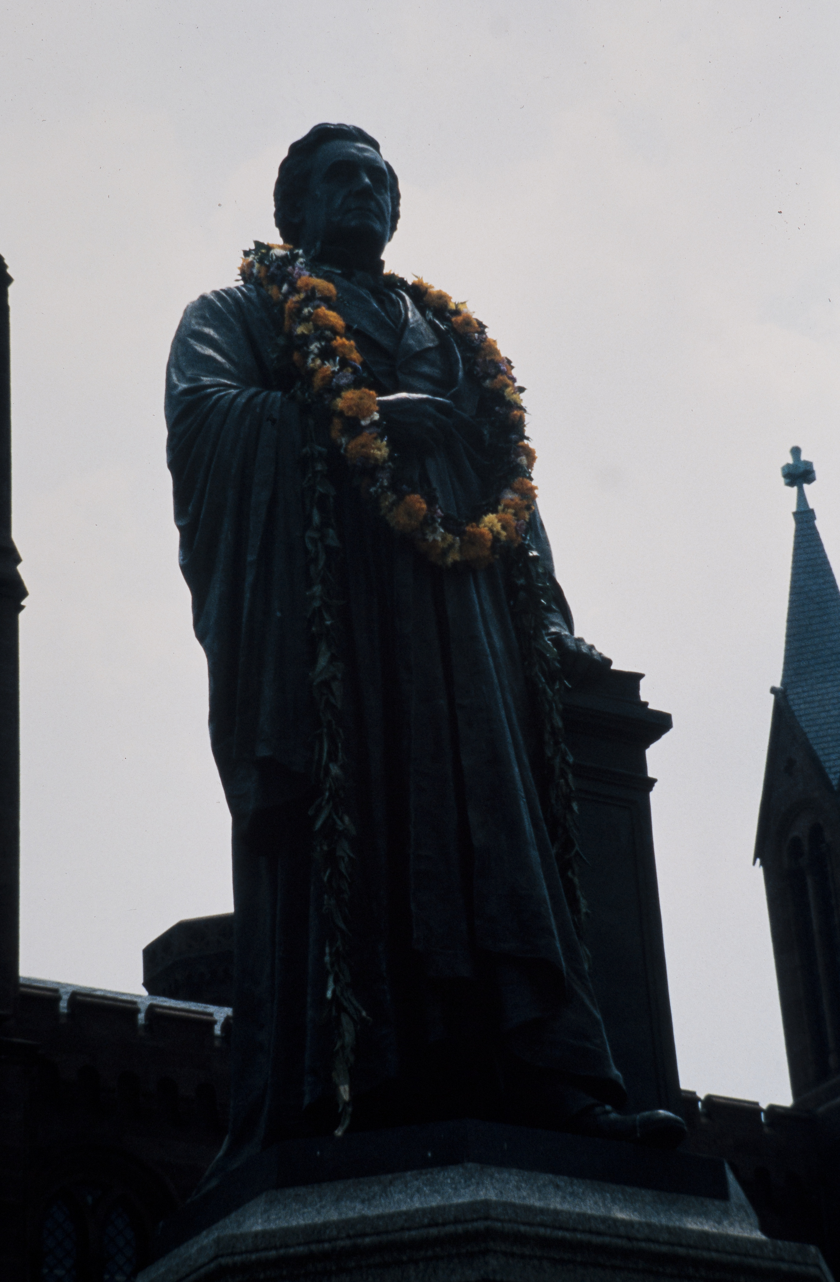 Bronze statue of Smithsonian Secretary Joseph Henry with two leis placed around its shoulders.