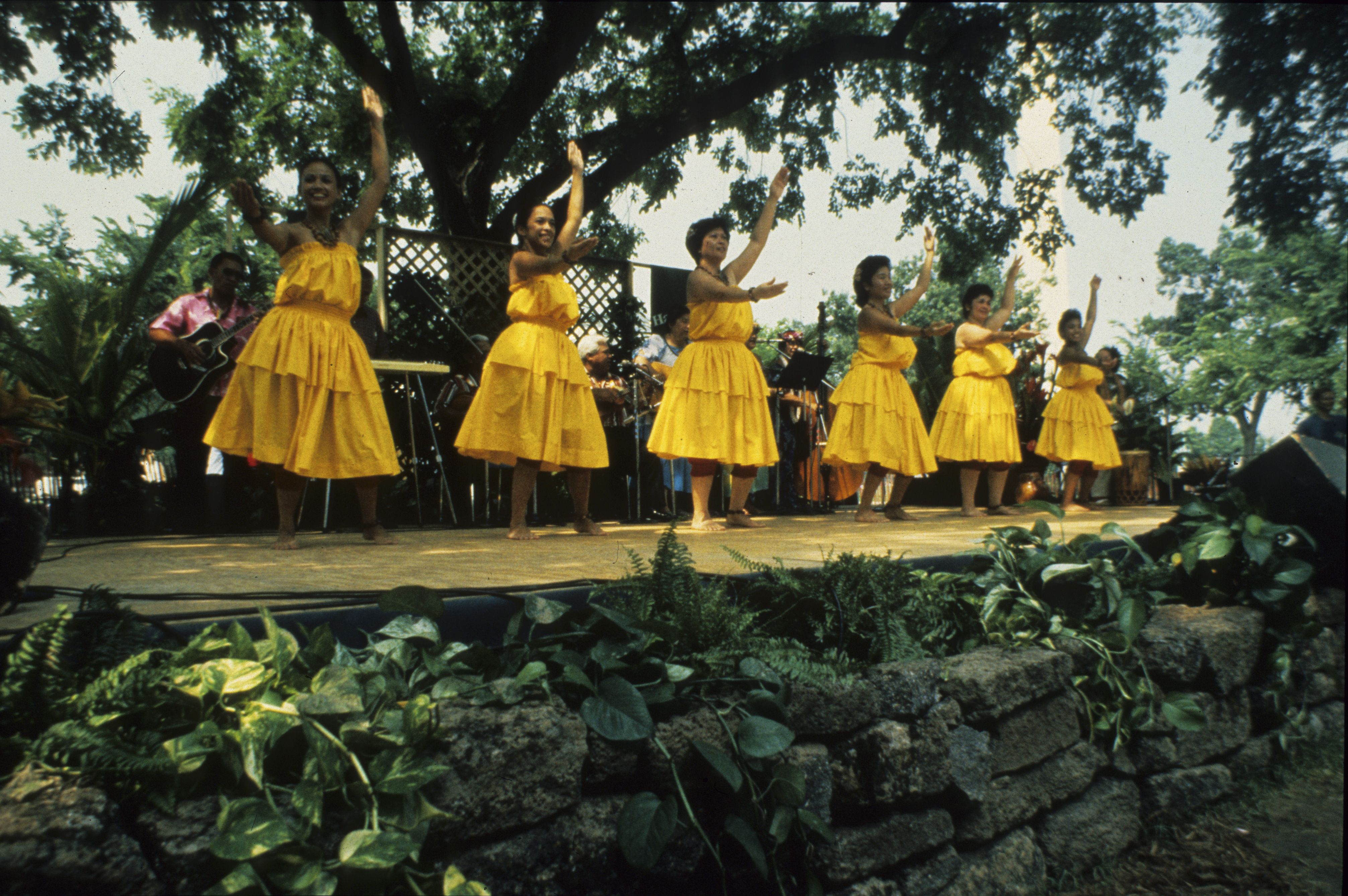 On a raised platform stage, six hula dancers in yellow dresses with arms raised.