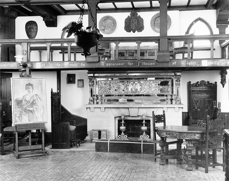 B&W photo of interior with fireplace, a portrait of a woman on an easel, and highly ornate wood furn