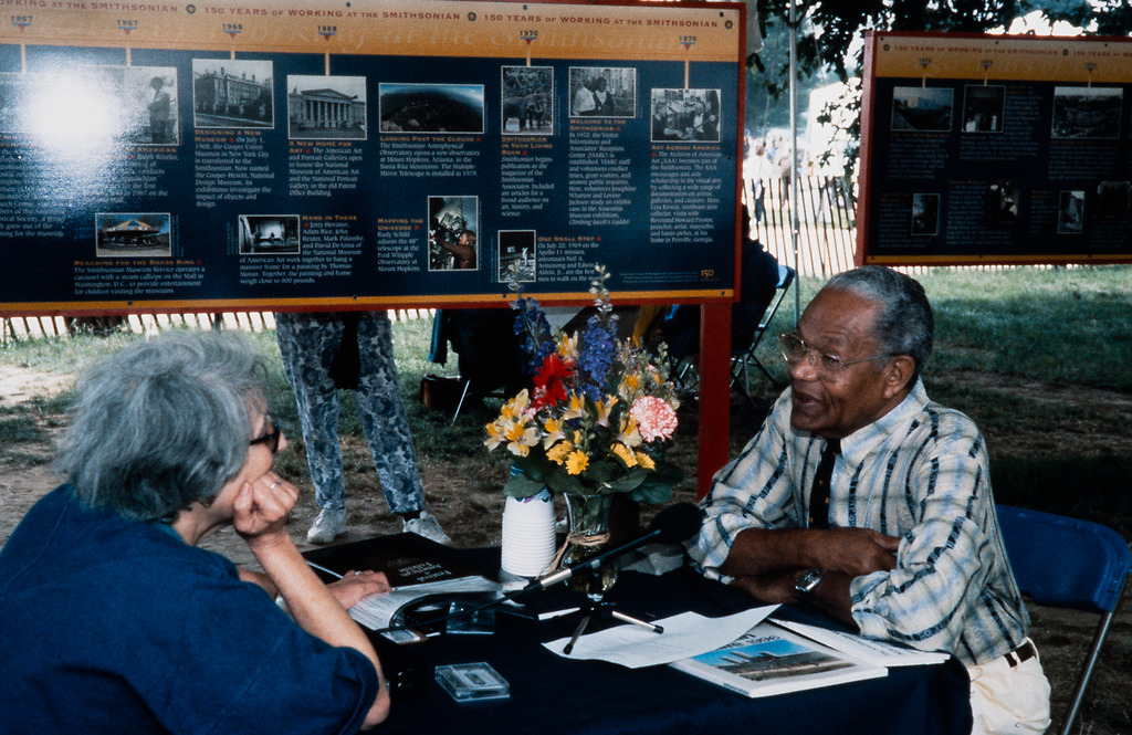 An older woman interviews an older man. A cassette tape is on the table in front of her and a microp