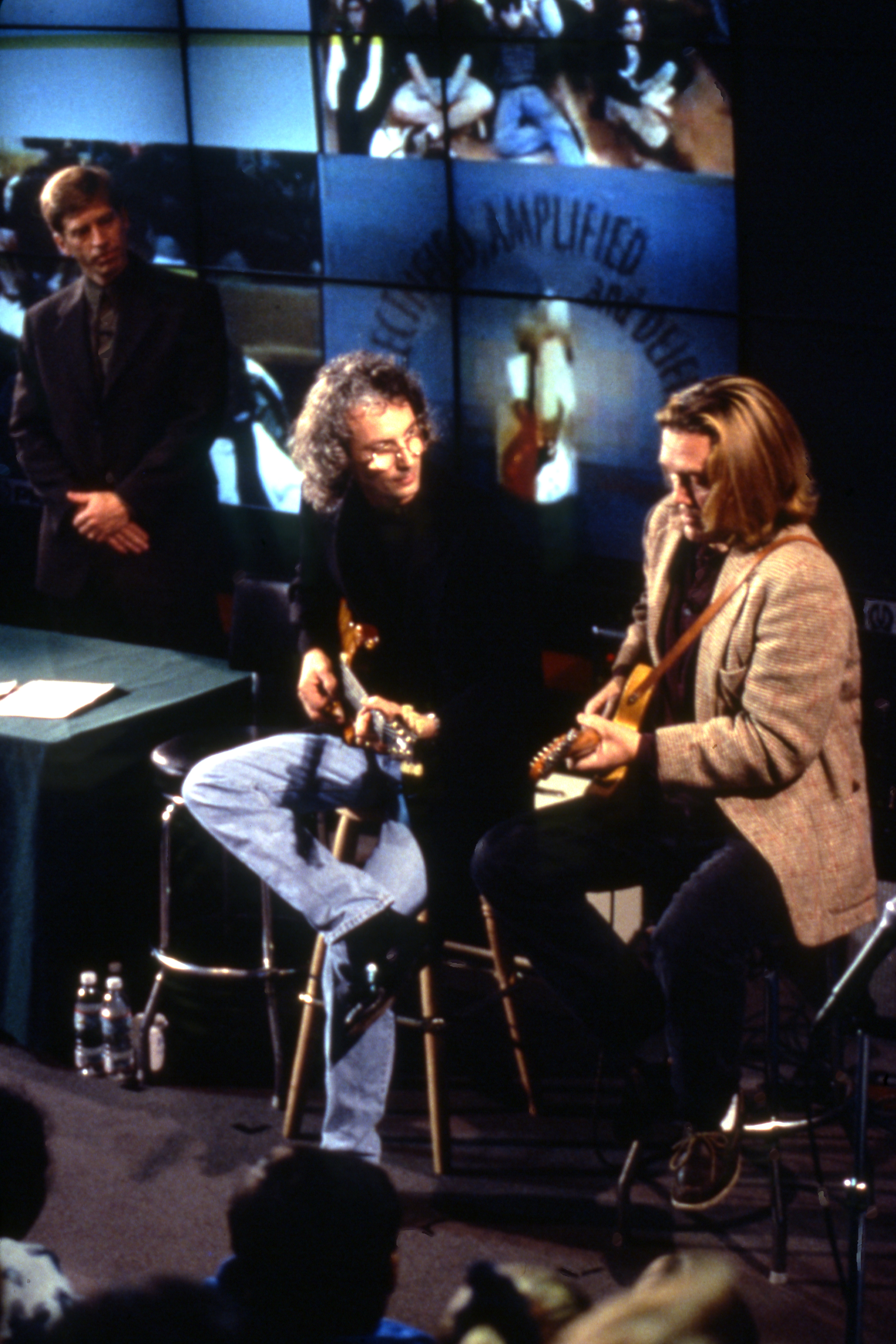 Guitar maker Paul Reed Smith and guitarist, G. E. Smith sitting on stools holding guitars.