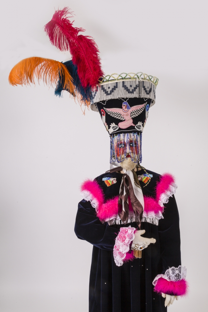 Fully dressed model in black robe with pink collar and sleeves and elaborate headdress with bright f