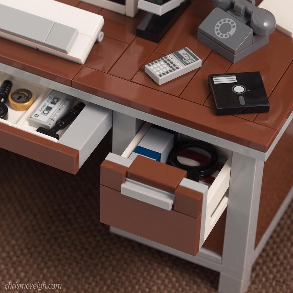 lego of desk with lego floppy disks, rotary phones, cassette tapes.