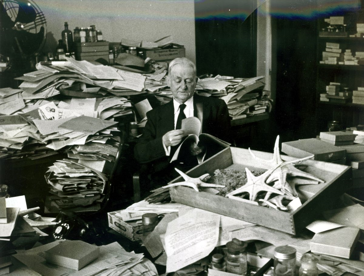 Black and white image of Austin Clark sitting at his desk, which is covered in piles of papers and m