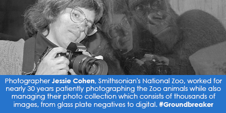 B&W portrait of woman holding camera, leaning against glass with gorilla face on the other side.