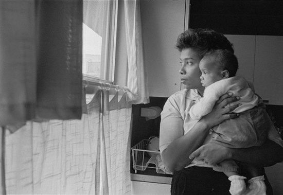 Black and white image of African American woman holding her baby, looking out the window.
