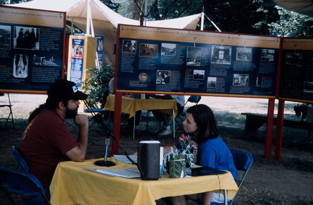 A young woman in a blue t-shirt interviews a man with a beard and long hair in a tented area. The ma