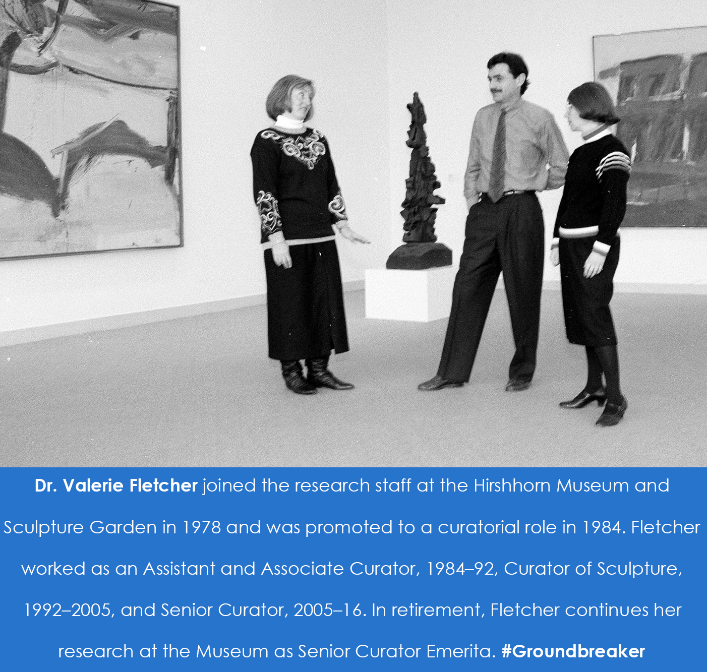 Valerie Fletcher stands and talks with two other people in a gallery space in front of a sculpture a