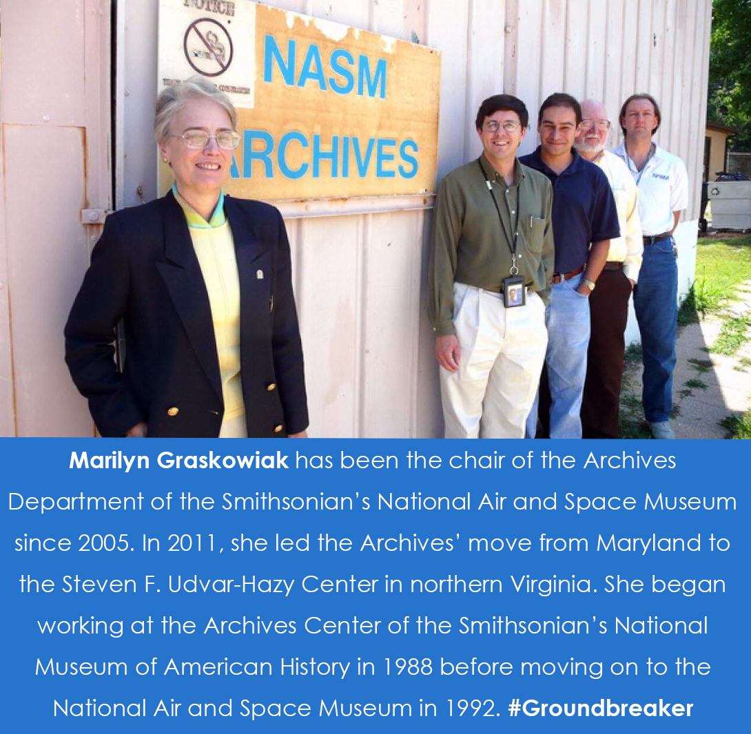 Graskowiak stands at the forefront in front of a NASM Archives sign and four men stand in the backgr