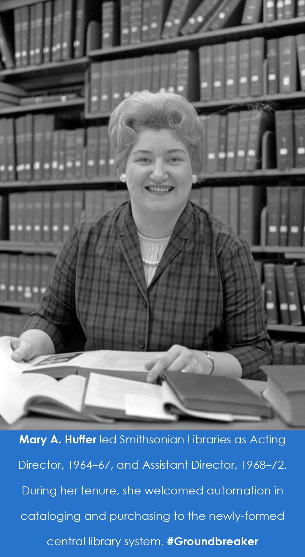 A woman sits at a desk in front of an open book.