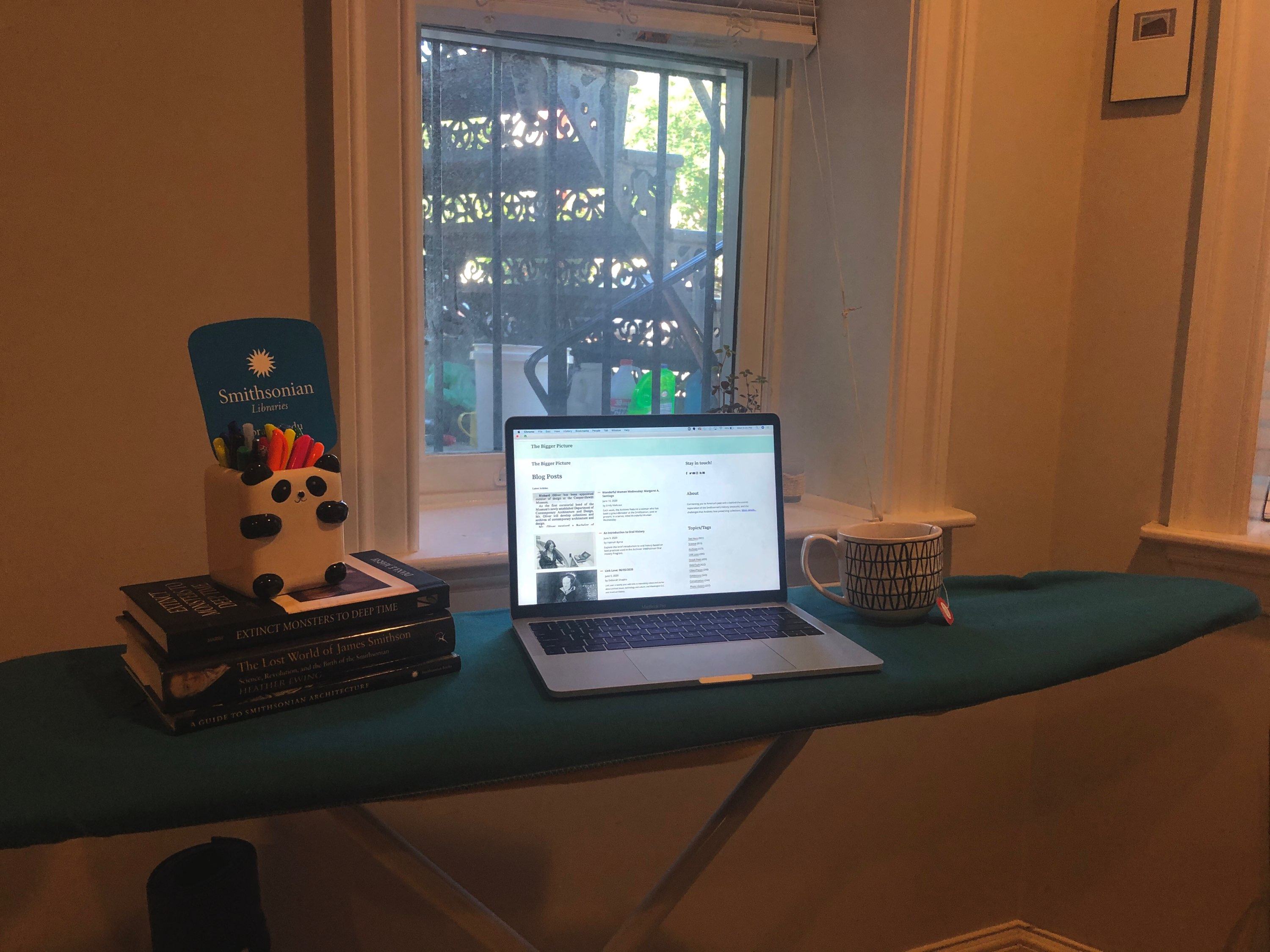 A laptop and books on an ironing board.