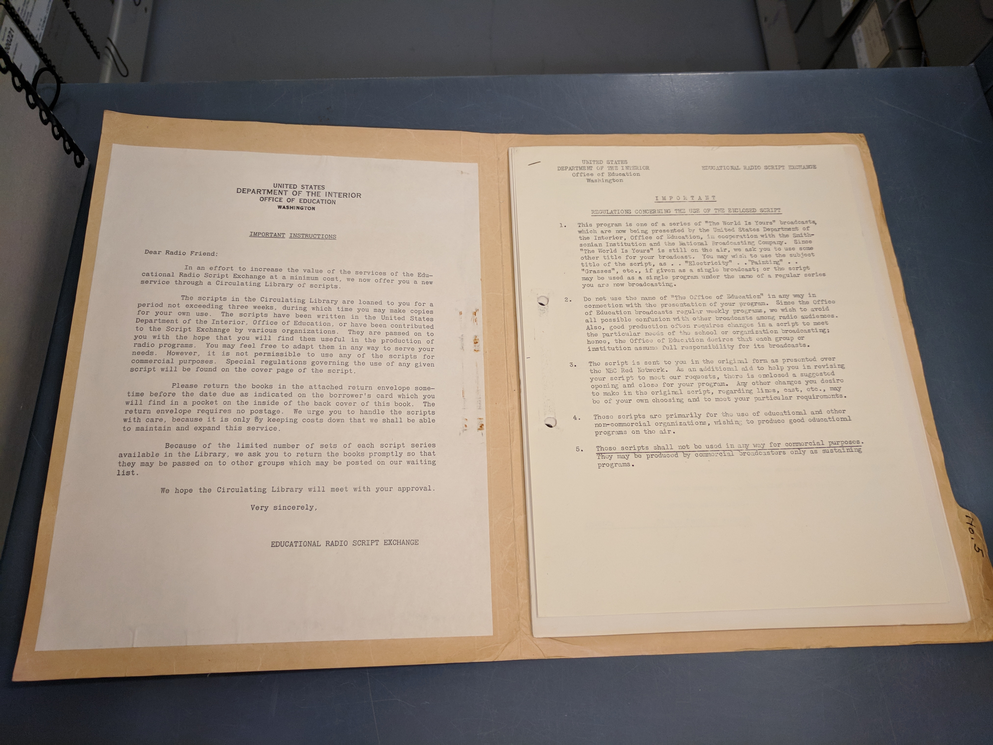 Manilla folder open on a grey metal table. The folder shows a single piece of paper on the left side
