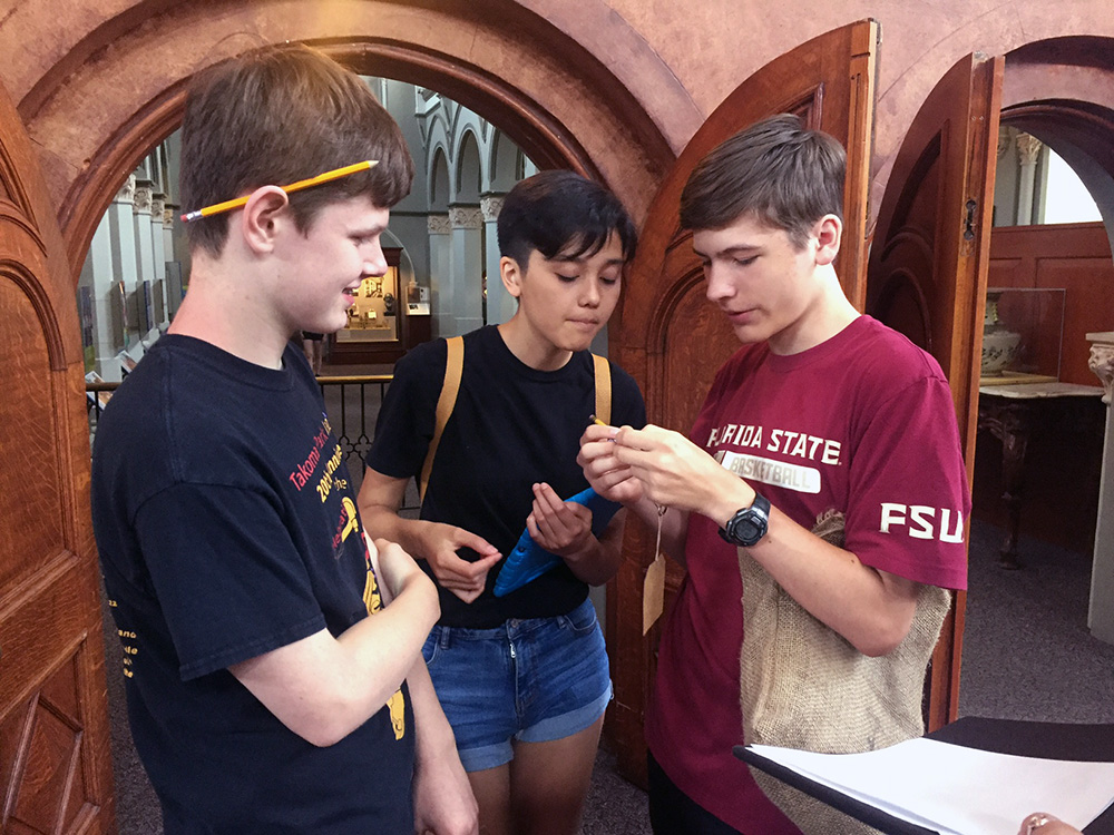 Three teens examining a hidden message on a pencil in front of gothic doors.