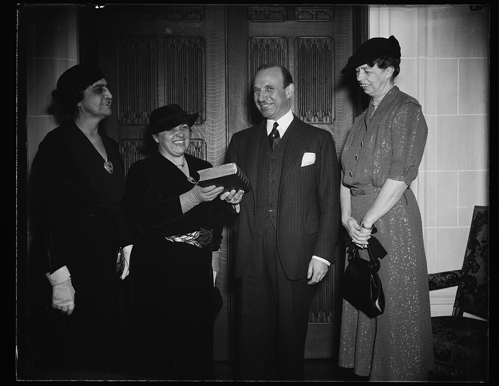Black and white photo of Marjorie B. Illig, presenting a book to Jule Henry as Eleanor Roosevelt loo