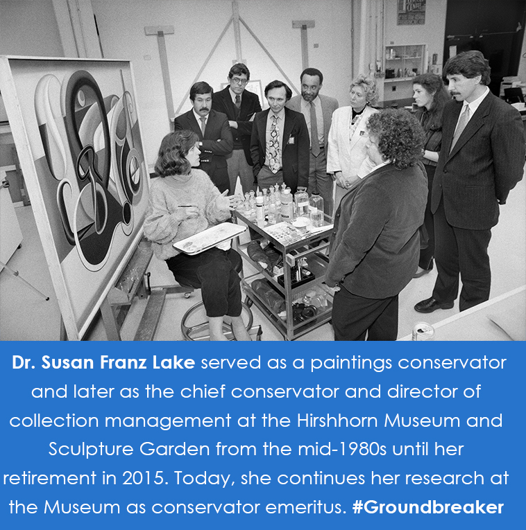 Lake sits in front of an abstract painting. A group of adults crowds around her.