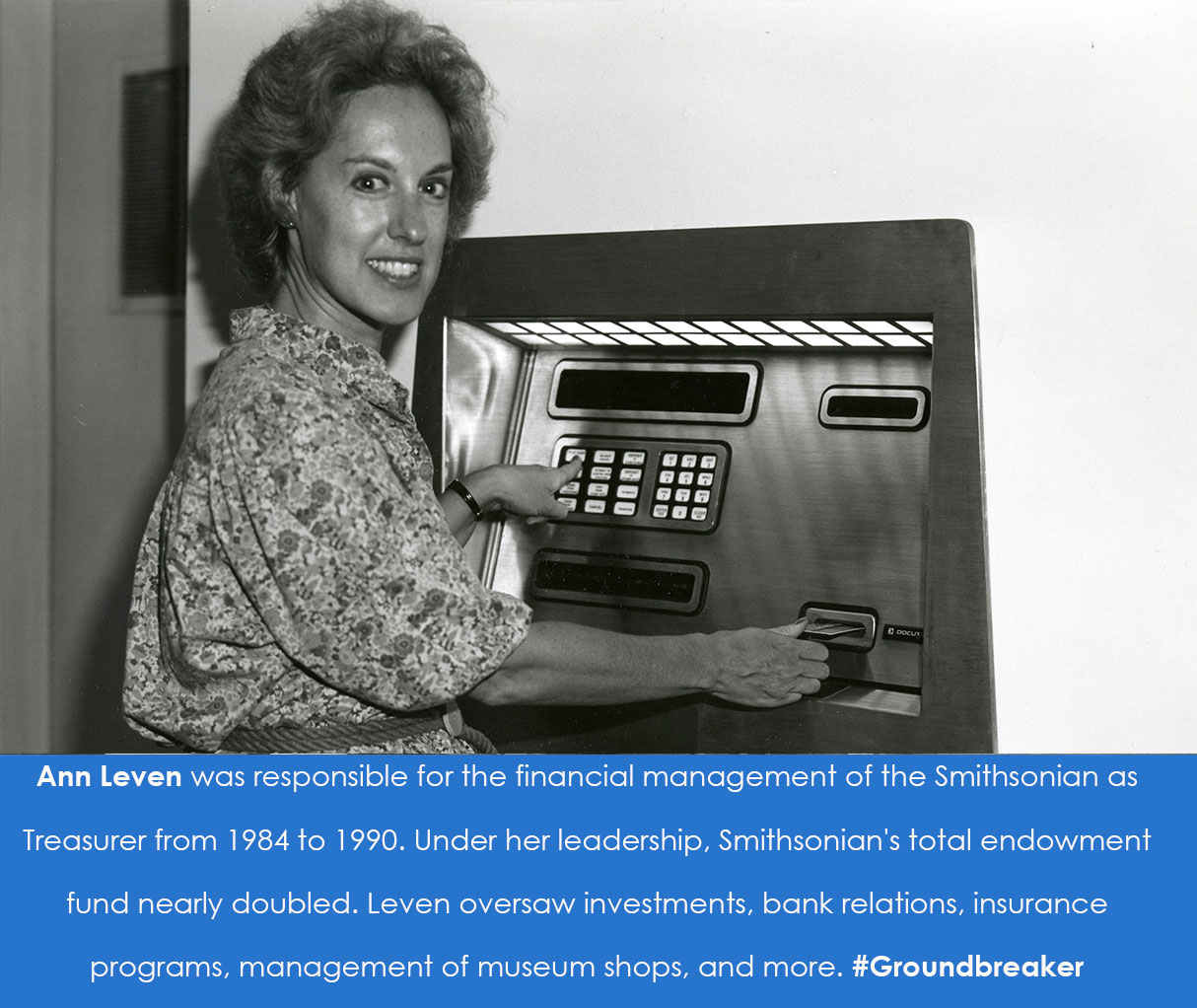 A woman holds a card up to a slot in an ATM machine. She turns to smile at the camera.