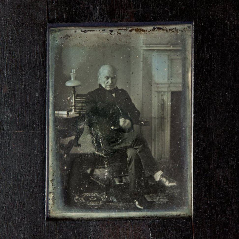 Worn portrait of man sitting cross-legged in wooden chair next to a table with a lamp and books.