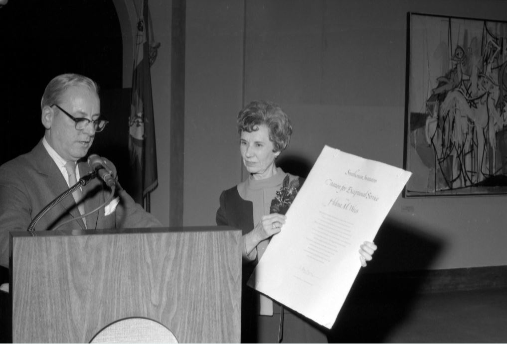 Man in front of podium talking with woman beside him holding large certificate