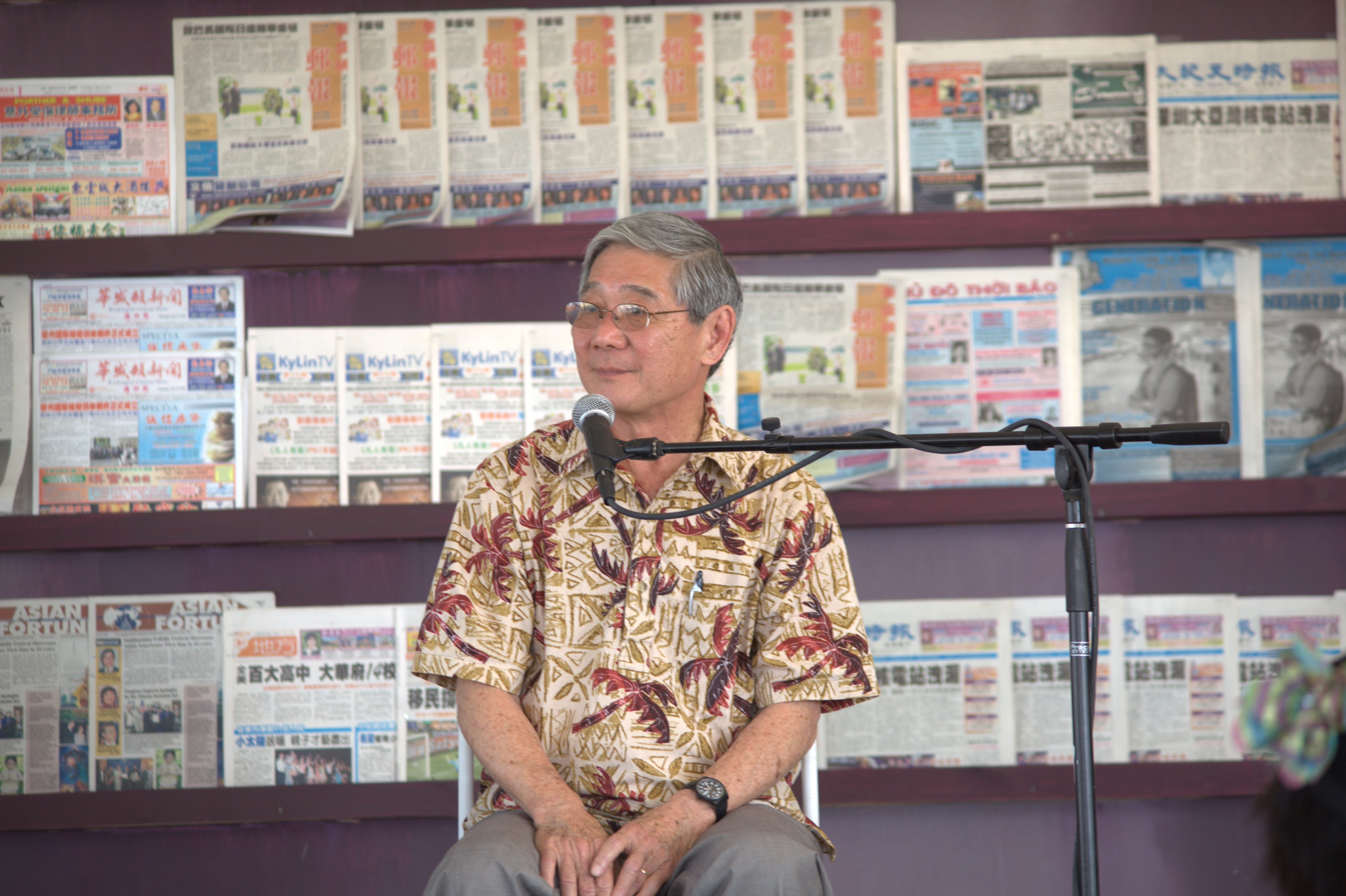 Seated man with microphone in front of him on stage with multilingual newspapers behind him.