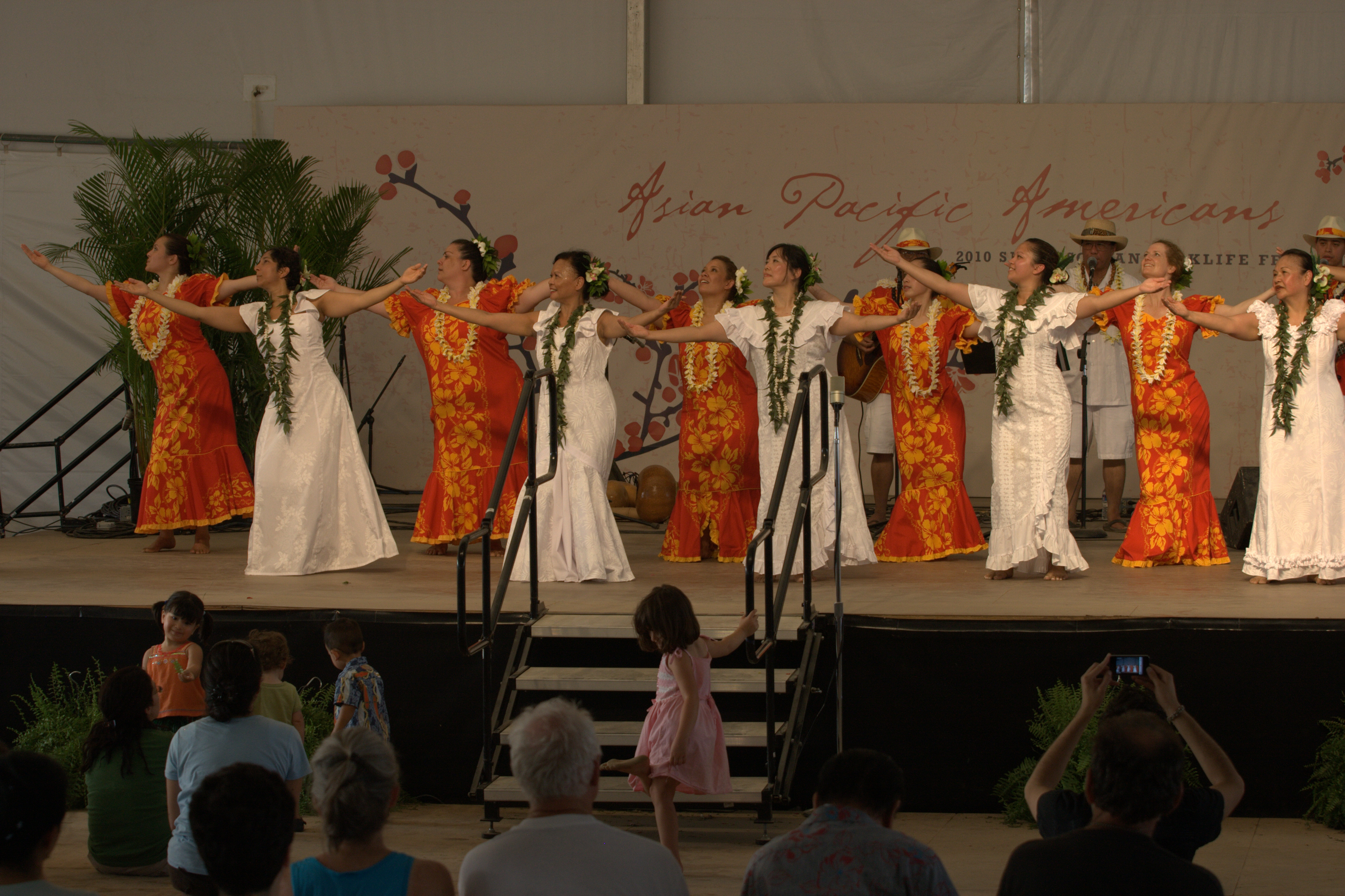 Hula dancers, some in white dresses and some in red and yellow dresses, on raised stage performing h
