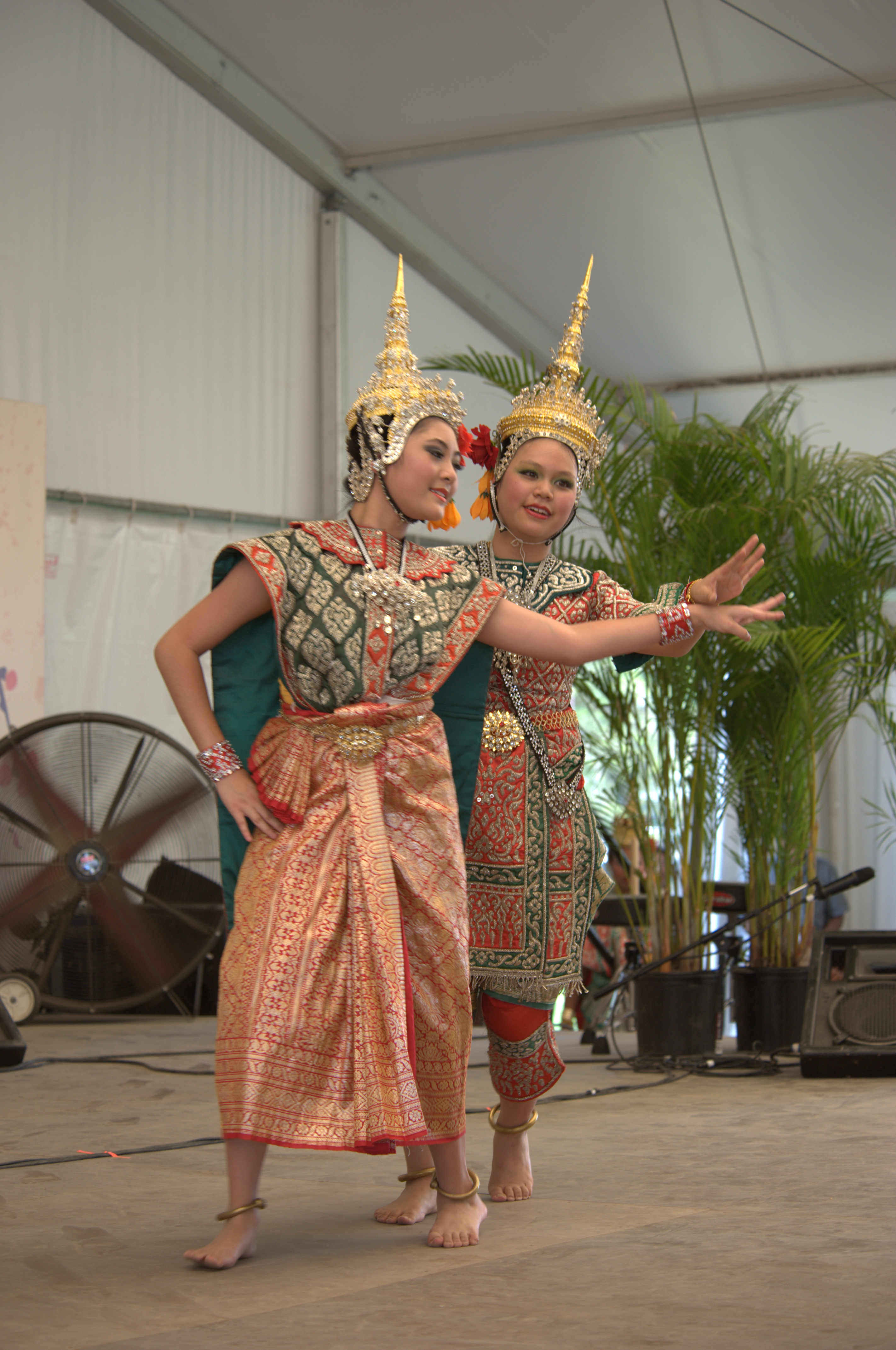 Two festival participants dancing with fan and plants behind them
