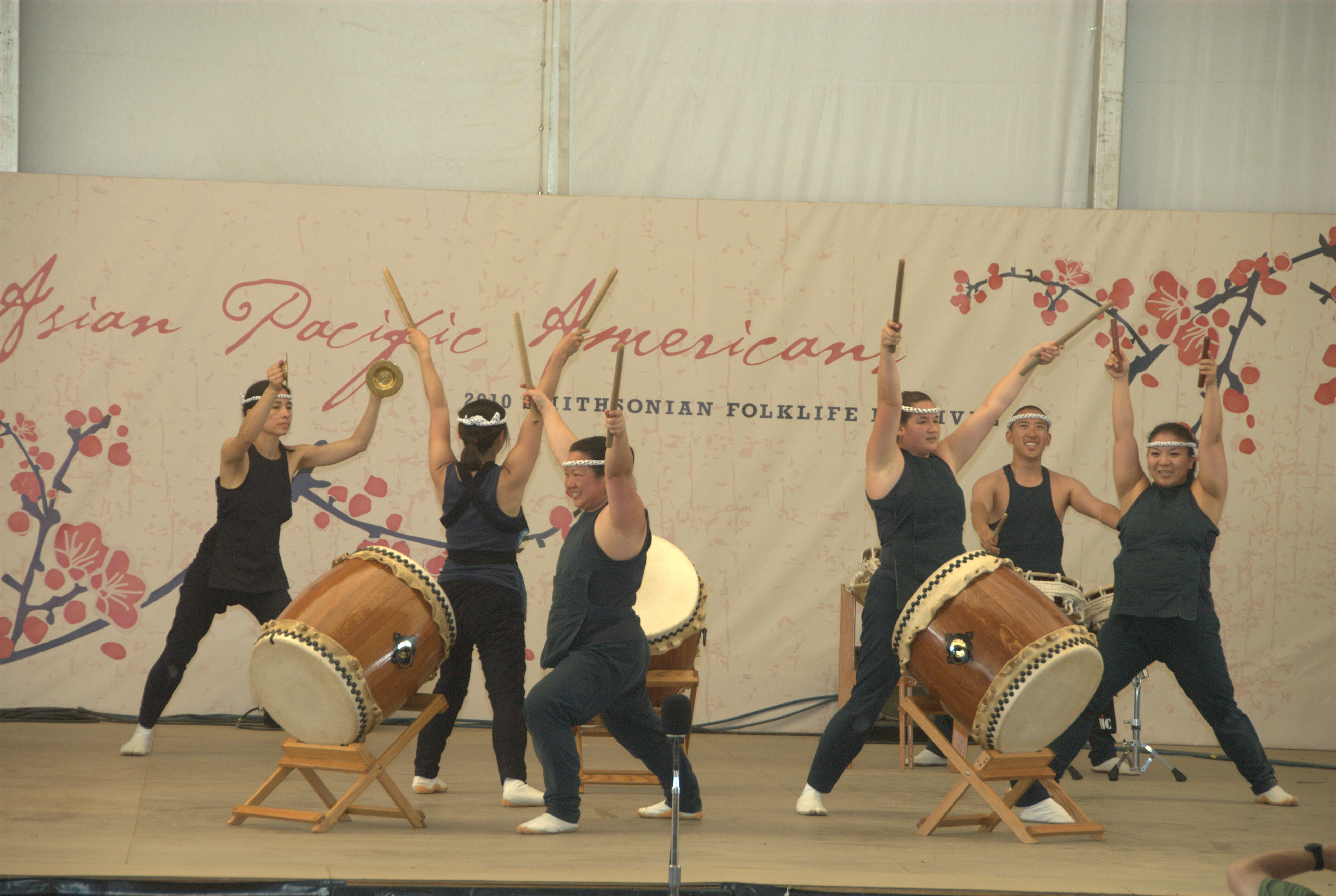 Festival participants with drums and drum sticks on stage with banner behind them.
