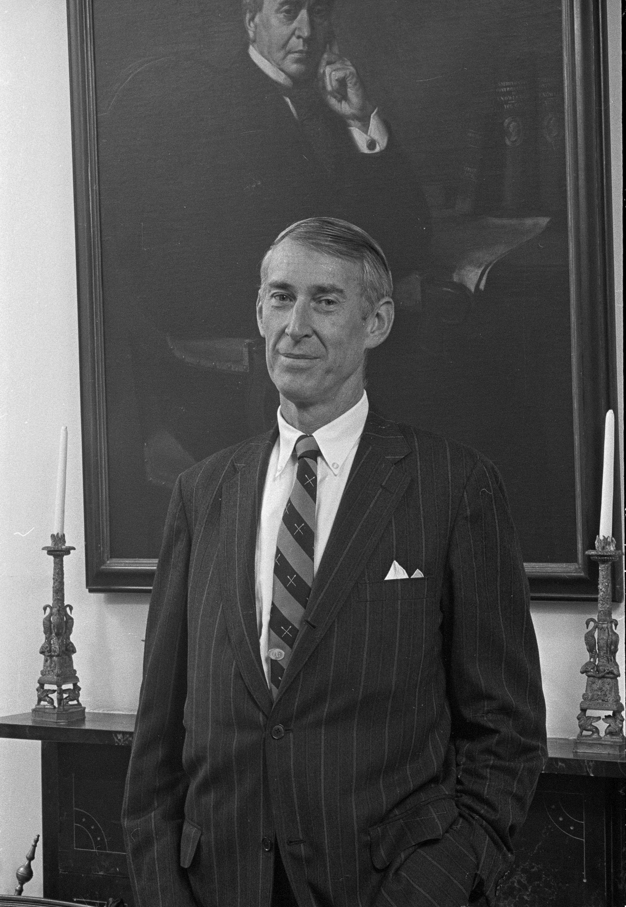Dr. David Challinor standing in front of a large painting of first Smithsonian Secretary Joseph Henr