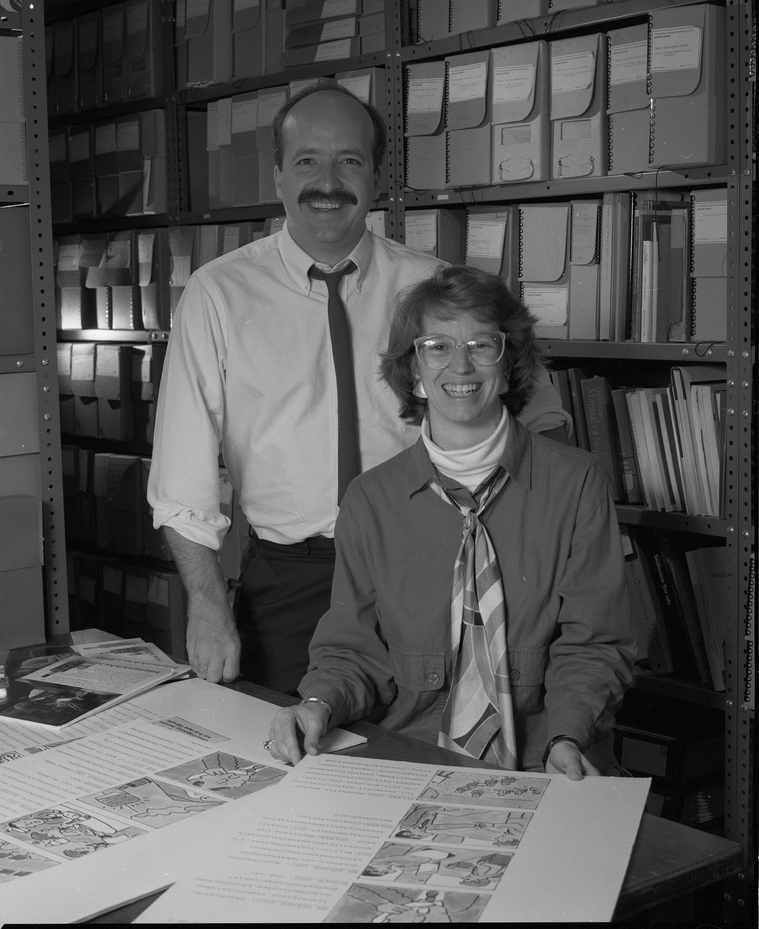A man and woman, Flaherty, look over story boards on a desk.