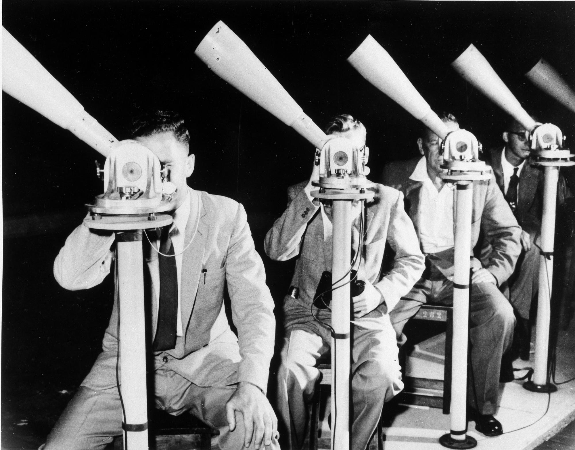 B&W photo of 4 men staggered peering through telescopes