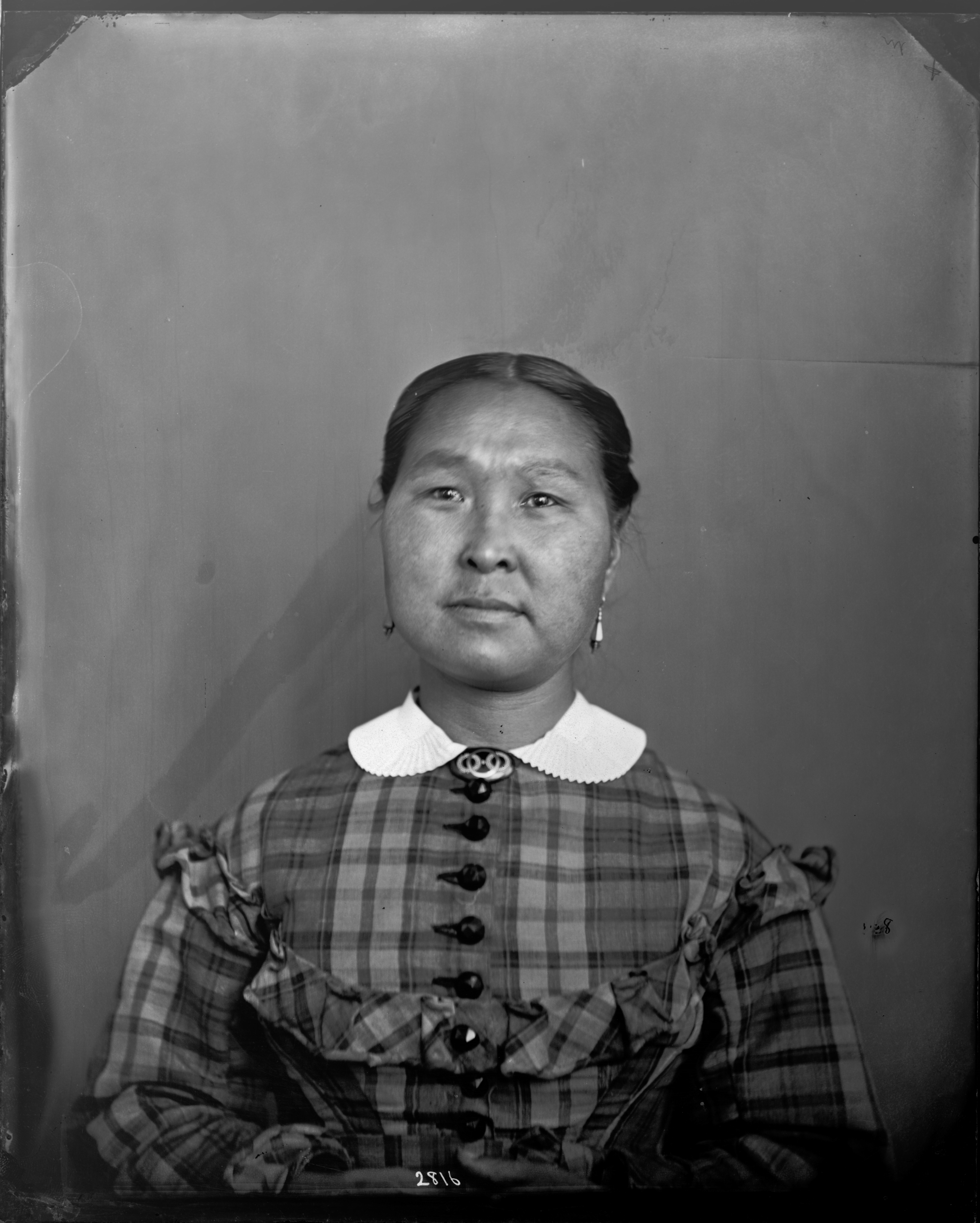 Portrait of Taqulittuq. Her hair is parted in the middle and pulled back into a bun. She is wearing