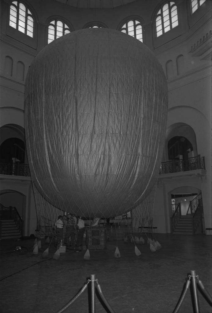 """Workers prepare a hot air balloon to hang in the Rotunda of the Arts and Industries Building. The centerpiece of the Charles Eames exhibit """"Photography and the City: The Evolution of an Art and a Science,"""" which opened June 6, 1968, the balloon was used to illustrate the method used to take the first aerial photo in the United States. Accession 11-008, Smithsonian Institution Archives, Neg. no. OPA-1353-15."""