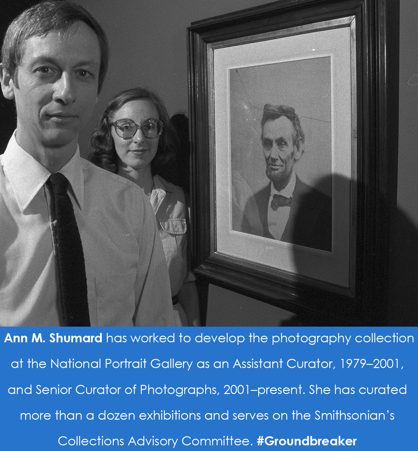 A woman stands behind a man, in the forefront. Both are standing near a portrait photograph of Abrah