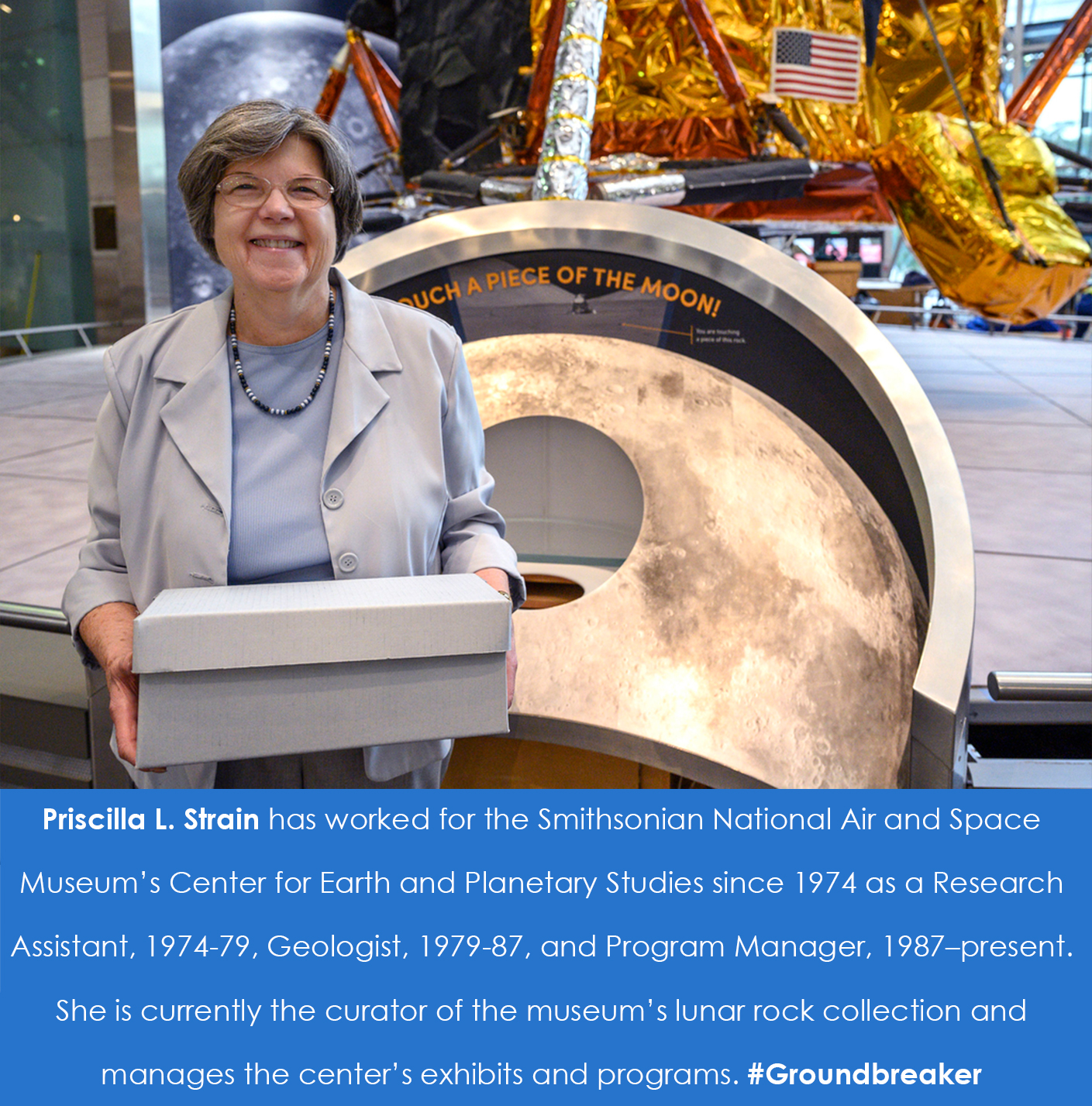 A woman holds a box and smiles at a camera. She is standing in front of a lunar rock sample.