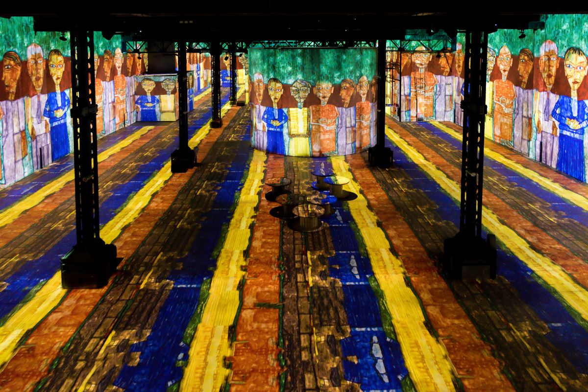 A large room with projections on the floor and walls with figure lining the side walls.