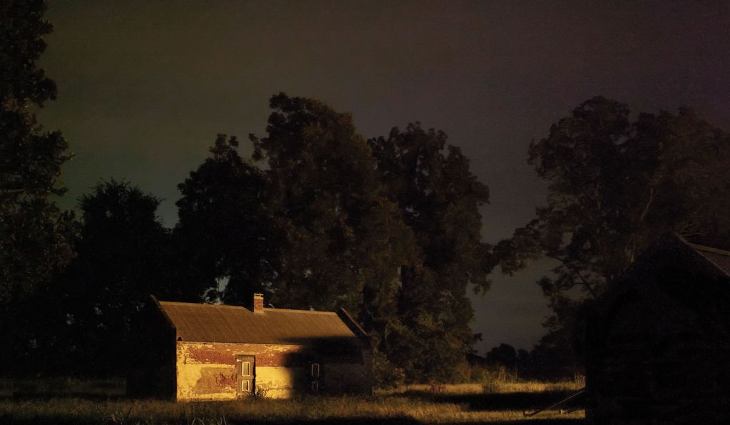 Color photograph of dilapidated house in dark light.