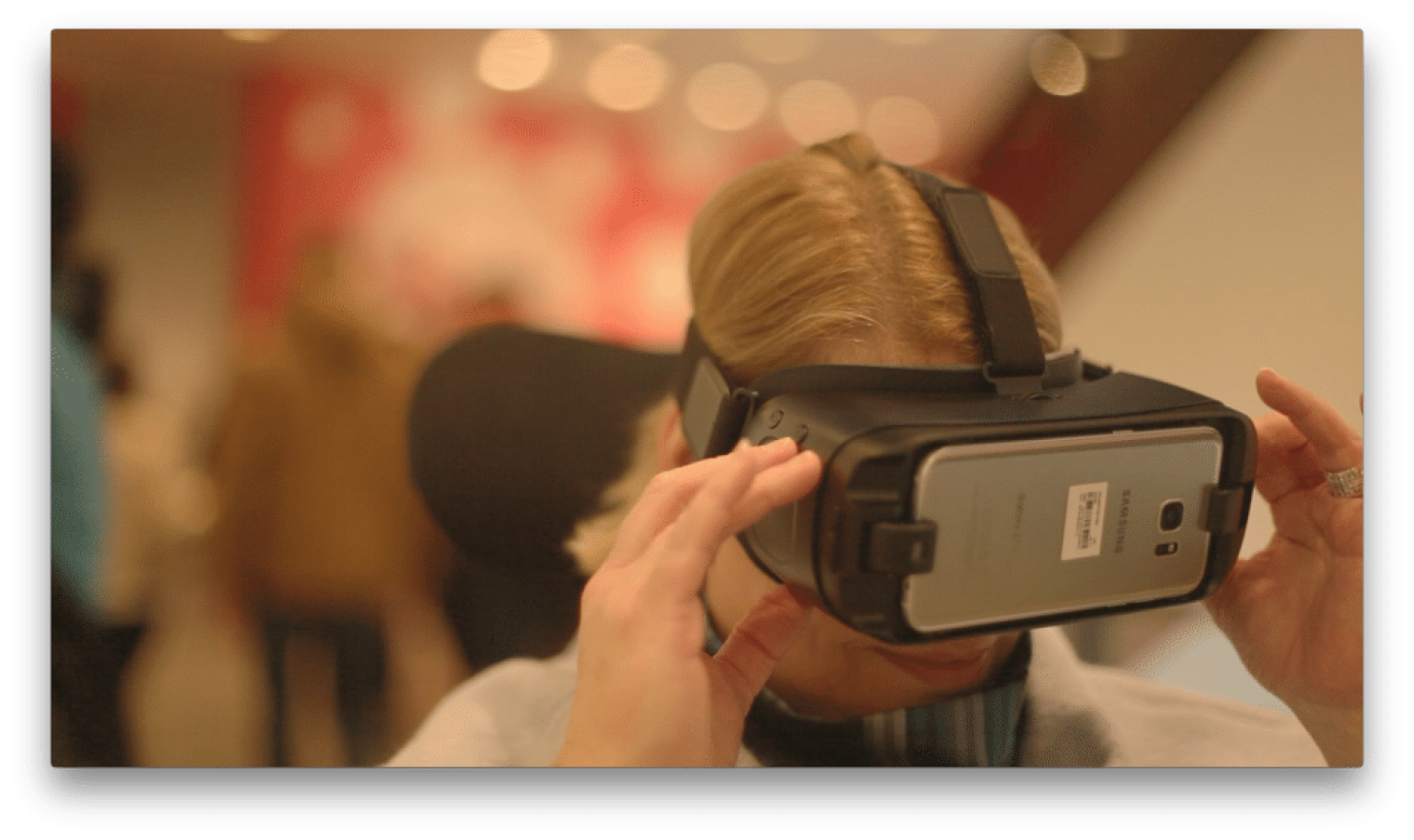 Color photo of woman using virtual headset smiling.